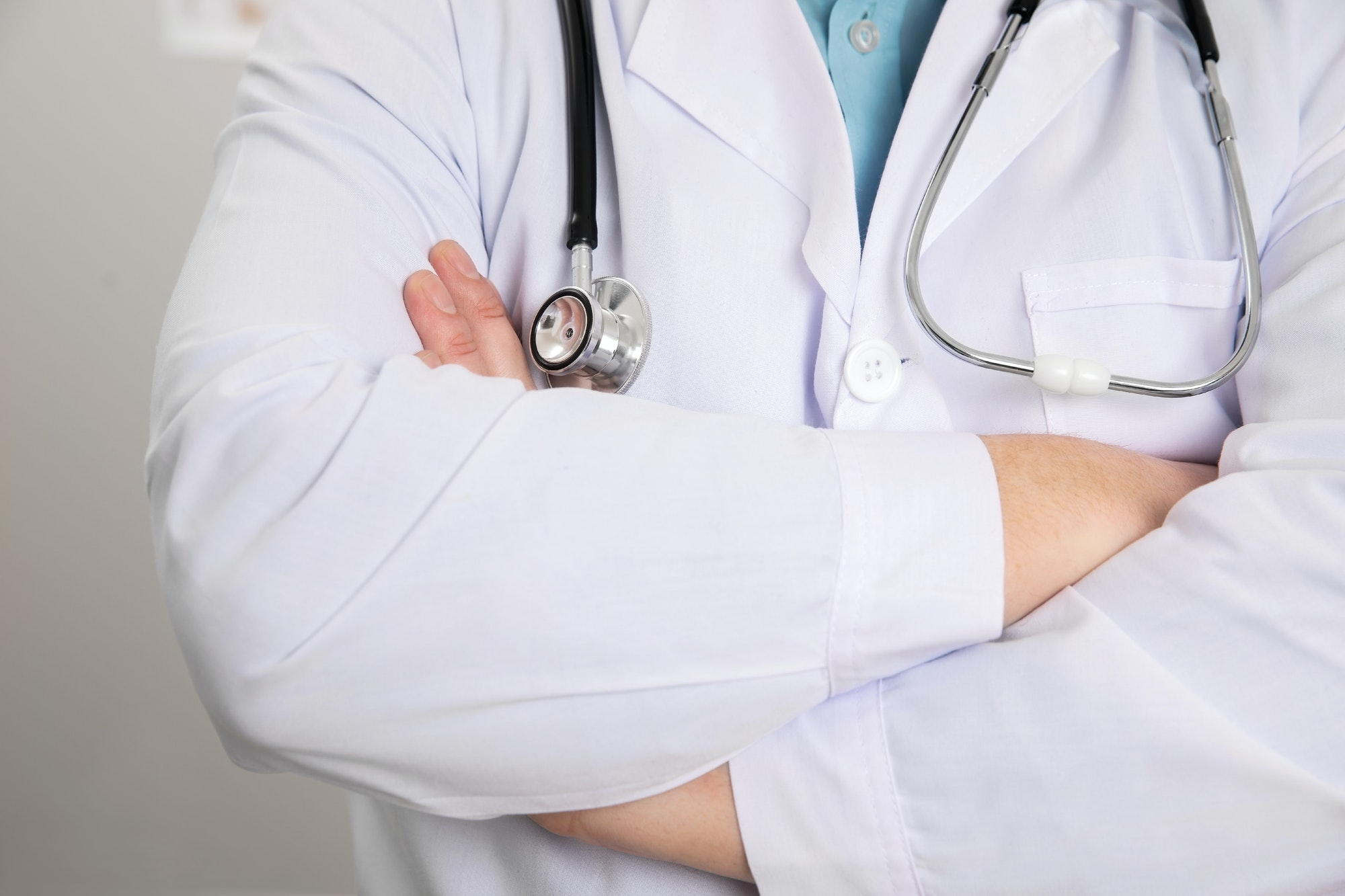 Male Doctor Standing With Arms Crossed In Clinic